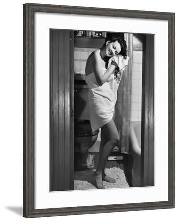 Woman Standing in Bathroom, Wrapped in Towel--Framed Photographic Print