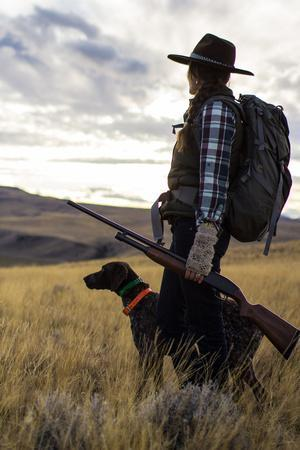 https://imgc.artprintimages.com/img/print/woman-stands-next-to-her-hunting-dog-looking-out-into-montana-s-vast-landscape_u-l-q1bb77j0.jpg?p=0