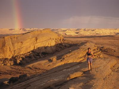 Woman Trail Running in a Rocky Landscape with a Rainbow-Bobby Model-Photographic Print