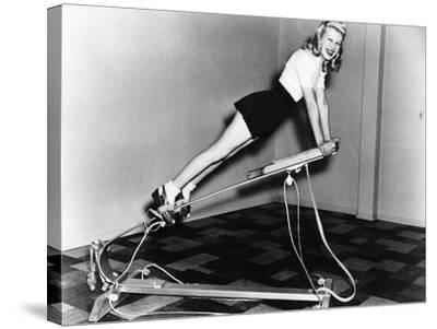 Woman Using Exercise Equipment--Stretched Canvas Print