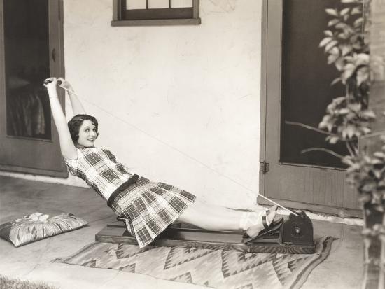 Woman Using Rowing Machine at Home--Photo