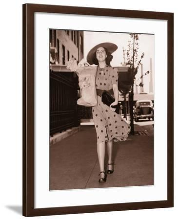 Woman Walking Down Street Carrying Grocery Parcel--Framed Photographic Print