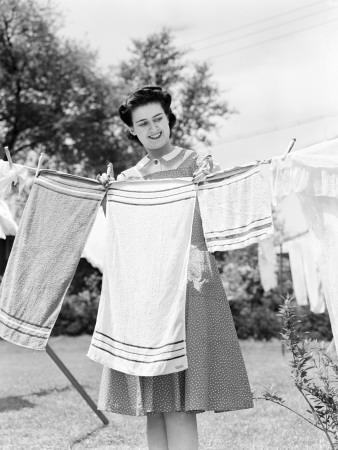 https://imgc.artprintimages.com/img/print/woman-wearing-a-white-collar-poka-dot-cotton-dress-while-pinning-a-towel-on-a-clothes-line_u-l-q10bpxn0.jpg?p=0