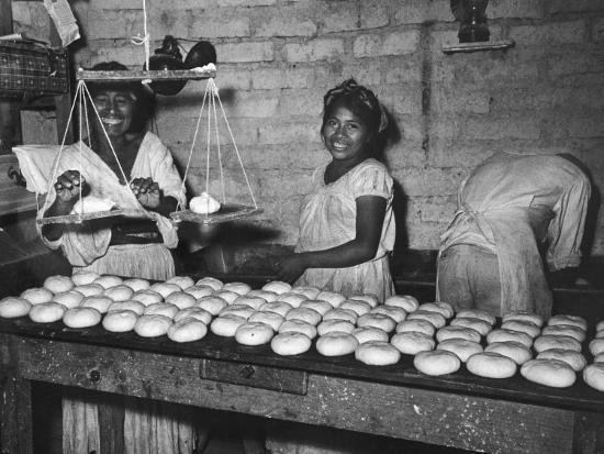 Women Stacking Loaves of Bread on Wooden Table, in Primitive Village of Zoogocho--Photographic Print