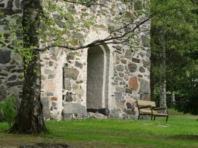 Wooden Bench in Peaceful Garden in Front of Stone Building--Photographic Print