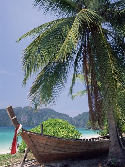 Wooden Boat Beneath Palm Trees on Beach, off the Island of Phuket, Thailand-Ruth Tomlinson-Photographic Print