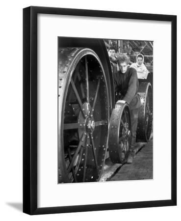 Workers Standing Amidst Large Metal Wheel Frames on Tractorstroi Tractor Factory Assembly Line-Margaret Bourke-White-Framed Premium Photographic Print