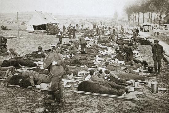 Wounded men waiting to be taken away to a clearing station, France, World War I, 1916-Unknown-Photographic Print