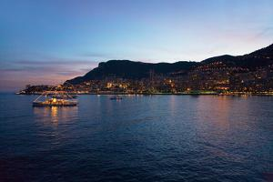 Yacht and seaside night view of Monte-Carlo with lights at dusk, in the Principality of Monaco,...