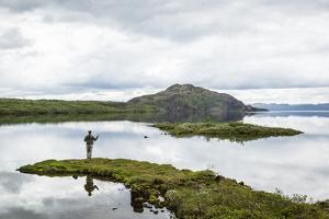 Man Fishing at Thingvallavatn Lake, Thingvellir (Pingvellir) National Park, Golden Circle, Iceland by Yadid Levy