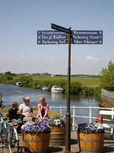 People Sitting on a Bench at Ribe City Center, Jutland, Denmark, Scandinavia, Europe by Yadid Levy