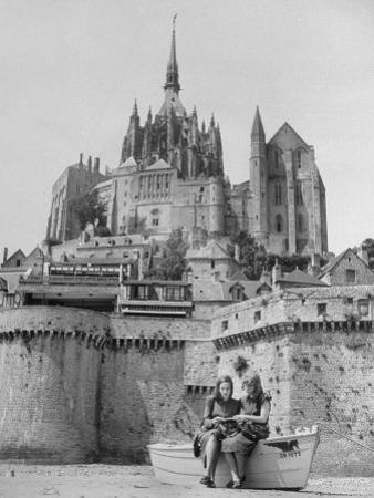 American Travelers Below France's Medieval Abbey at Mont Saint Michel Reading Together from a Book