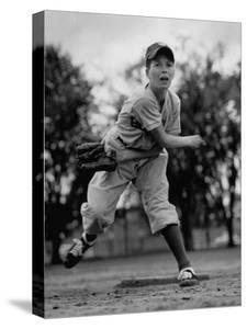 Boy Playing a Game of Little League Baseball by Yale Joel