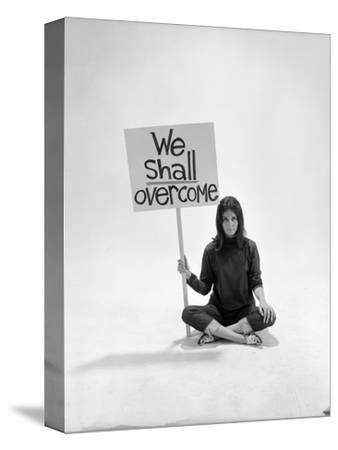 "Studio Photos of Gloria Steinem Sitting on Floor with Sign That Says 'We Shall Overcome"", 1965"