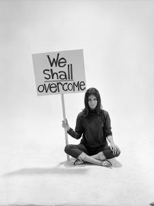 """Studio Photos of Gloria Steinem Sitting on Floor with Sign That Says 'We Shall Overcome"""", 1965 by Yale Joel"""