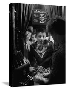 Teenage Boy Peering Into Window of Ticket Booth at a Movie Theater by Yale Joel