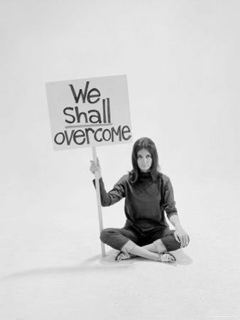 """Writer Gloria Steinem Sitting on Floor with Sign """"We Shall Overcome"""" Regarding Pop Culture"""
