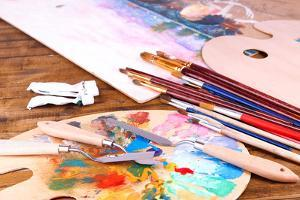 Artistic Equipment: Paint, Brushes and Art Palette on Wooden Table by Yastremska