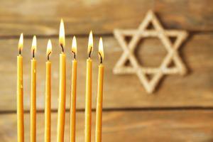 Hanukkah Candle on Wooden Background by Yastremska