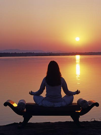 Yoga on a Saddle Bench Watching the Sun Go Down across the Zambesi River, Zambia-John Warburton-lee-Photographic Print