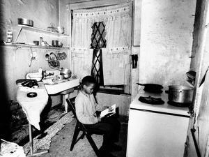 Young African American Studies by Kitchen Stove Because His Apartment Is Without Heat