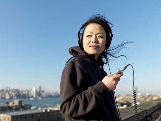 Young Asian Woman Listens to Her Headphones While Looking Away-xPacifica-Photographic Print
