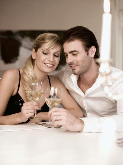 Young Couple Clinking Glasses of White Wine- Sporrer & Skowronek-Photographic Print