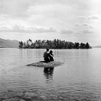 https://imgc.artprintimages.com/img/print/young-couple-embracing-on-small-rock-protruding-from-the-waters-of-lake-george_u-l-p440zj0.jpg?artPerspective=n
