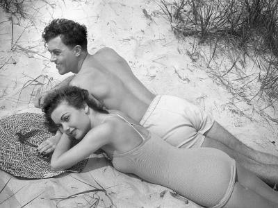 Young Couple in Bathing Suits Lying on Sand-George Marks-Photographic Print