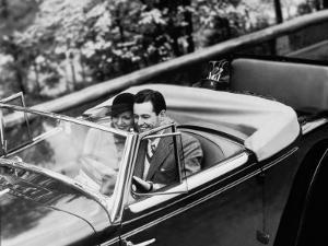 Young Couple in Vintage Soft Top Car With Golf Clubs on Back Seat