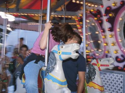 Young Couple Kissing on Carousel--Photographic Print