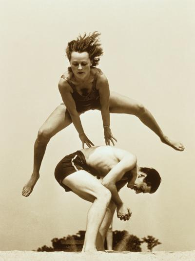 Young Couple Playing Leapfrog at Beach--Photographic Print