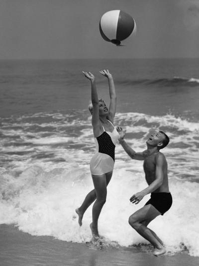 Young Couple Playing With Beach Ball at Water's Edge--Photographic Print