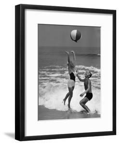 Young Couple Playing With Beach Ball at Water's Edge