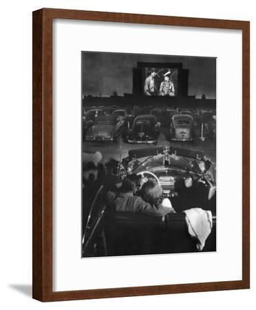 Young Couple Snuggling in Convertible as They Watch Large Screen Action at a Drive-In Movie Theater-J. R. Eyerman-Framed Premium Photographic Print
