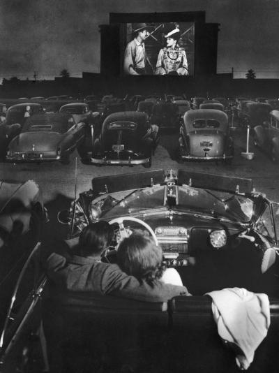 Young Couple Snuggling in Convertible as They Watch Large Screen Action at a Drive-In Movie Theater-J^ R^ Eyerman-Photographic Print
