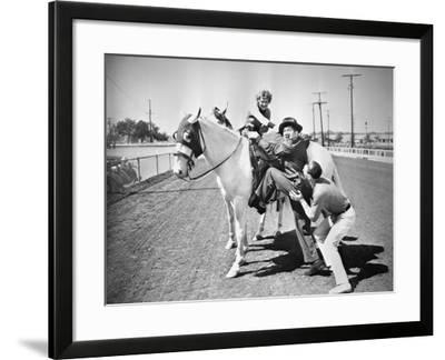 Young Couple Trying to Help a Man Get onto His Horse--Framed Photo