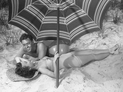 Young Couple Under Beach Umbrella-George Marks-Photographic Print
