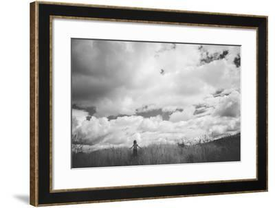 Young Girl Standing in a Field with Clouds-Clive Nolan-Framed Photographic Print