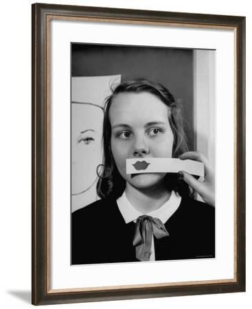 Young Girl Trying to Determine Which Lipstick Color Will Look Right with Her Complexion-Nina Leen-Framed Photographic Print