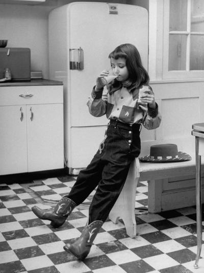 Young Girl Wearing Cowgirl Outfit Drinking Milk and Eating Sandwich in Kitchen-Nina Leen-Photographic Print