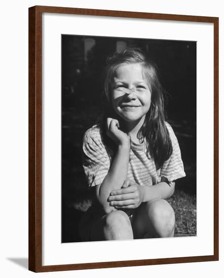Young Girl with Long Hair and Raggedy Shirt, Smiling, Wearing Seed Pod on Nose-Ralph Morse-Framed Photographic Print