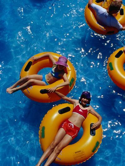 Young Girls Floating in Rubber Rings in Swimming Pool, Gold Coast, Australia-Richard I'Anson-Photographic Print
