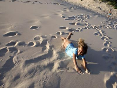 Young Girls Rolling Down Sand Dune-Cathy Finch-Photographic Print