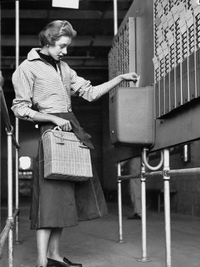 Young Lady Modeling New Line of Clothing While Getting Her Time Card Punched-Yale Joel-Photographic Print