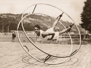 Young Man Doing Stunts on Exercise Wheel