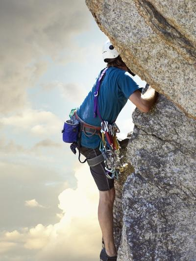 Young man rock climbing up a vertical cliff--Photographic Print
