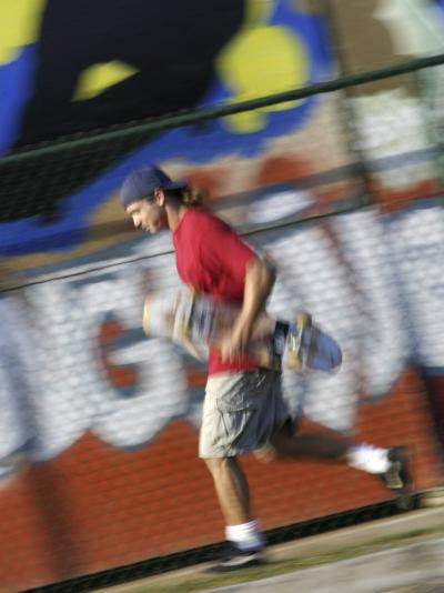 Young Man Running with Skateboard--Photographic Print