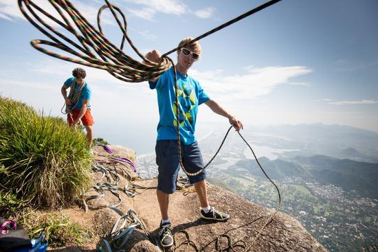 Young Man Standing on Top of the Mountain Holding Rope for Slacklining-Keith Ladzinski-Photographic Print