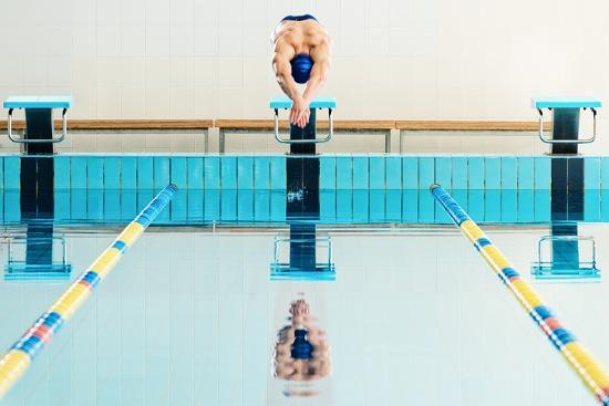 Young Muscular Swimmer Jumping from Starting Block in a Swimming Pool  Photographic Print by NejroN Photo | Art.com
